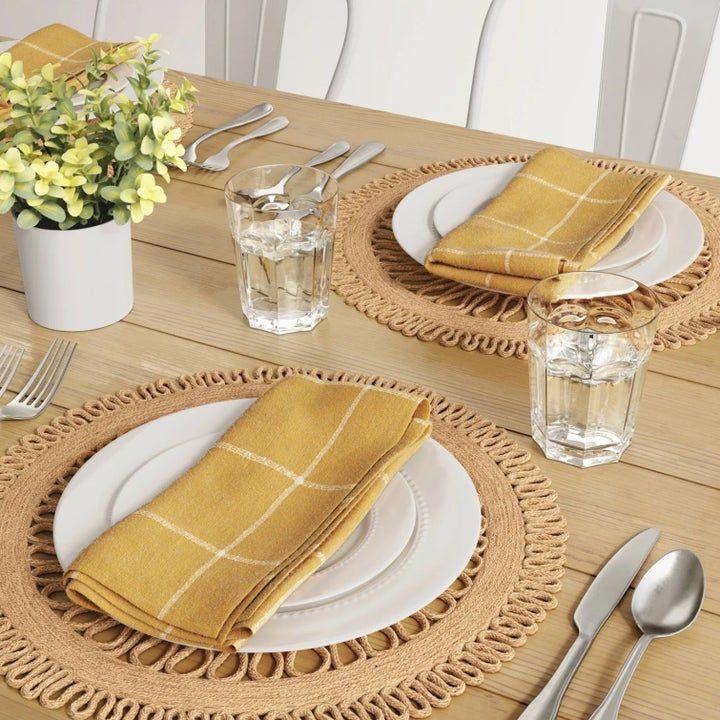 two of the mats on a wooden table with white plates stacked on them and yellow napkins on top of the plates. and glasses of water, silverware, and a table plant next to them.
