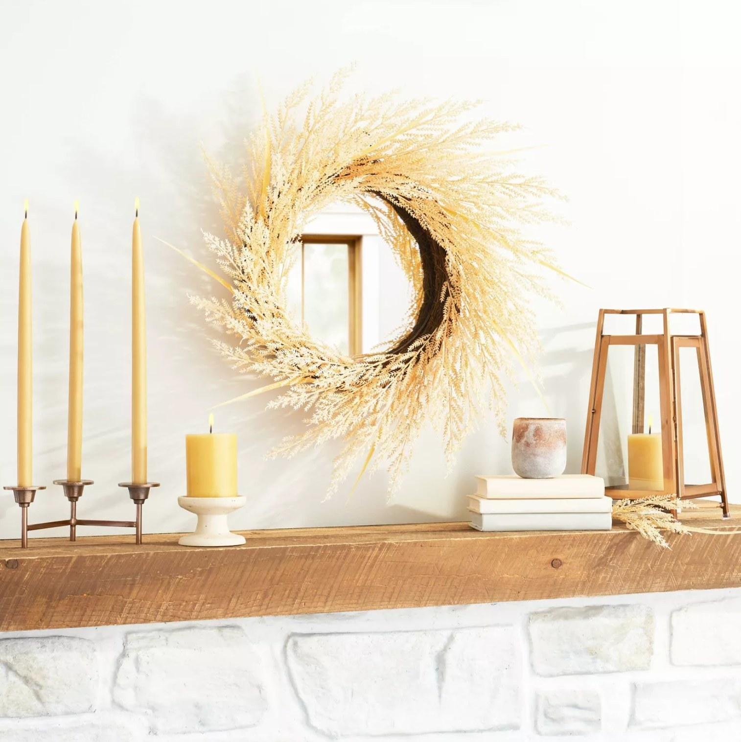 the faux plant wreath hanging around a circle mirror on a wall with candles, books, and other decorations on the wooden hearth beneath it
