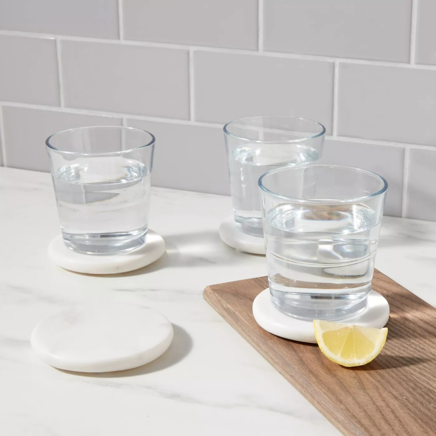 the white marble coasters on a white marble counter with glasses full of water on three of them and a lemon wedge next to a coaster with a glass on a wooden tray