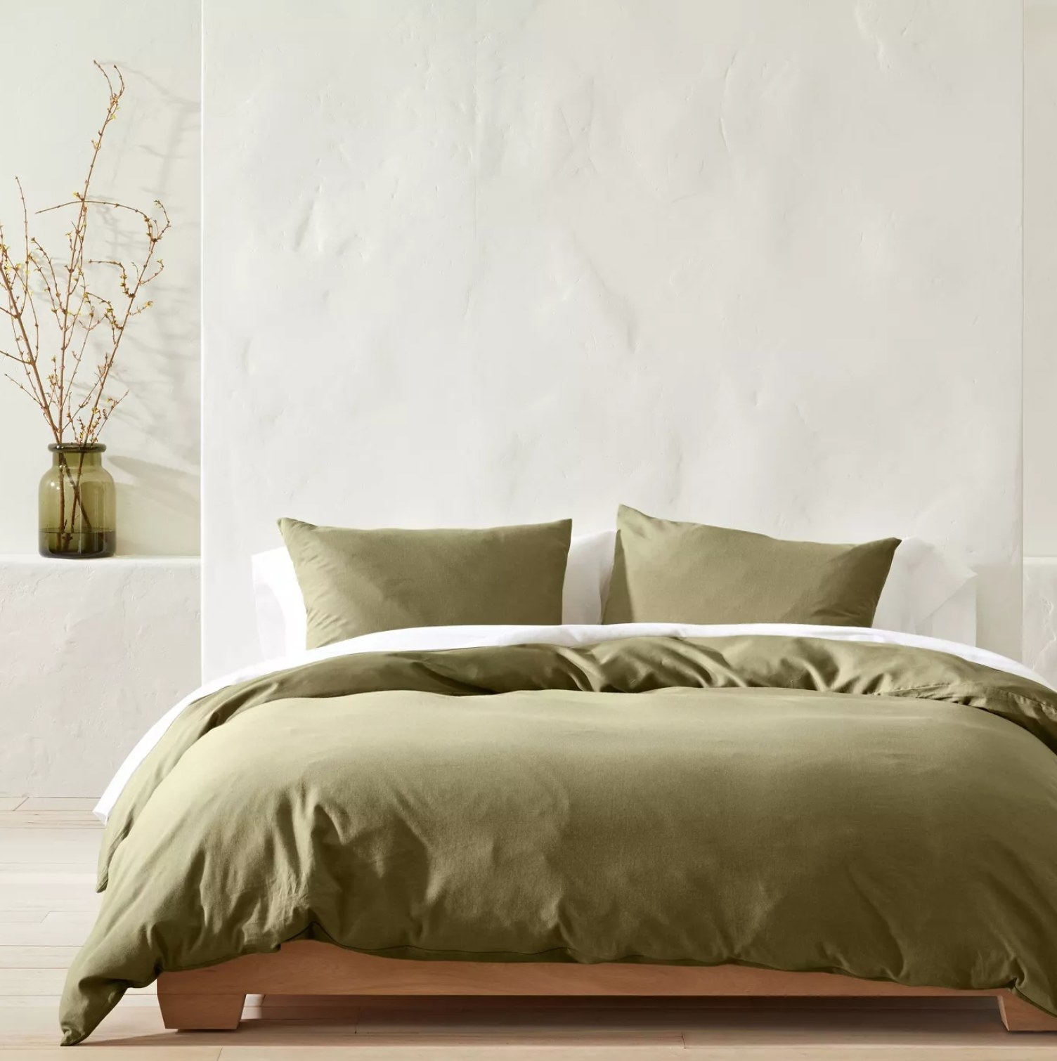 the sage green comforter and sham set on a bed with white stone walls behind it and a green planter next to it