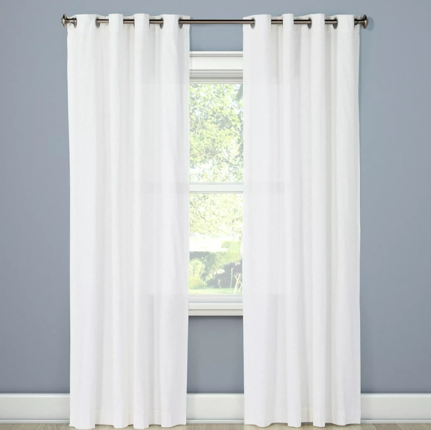 the white curtains hanging over a window against a blue wall