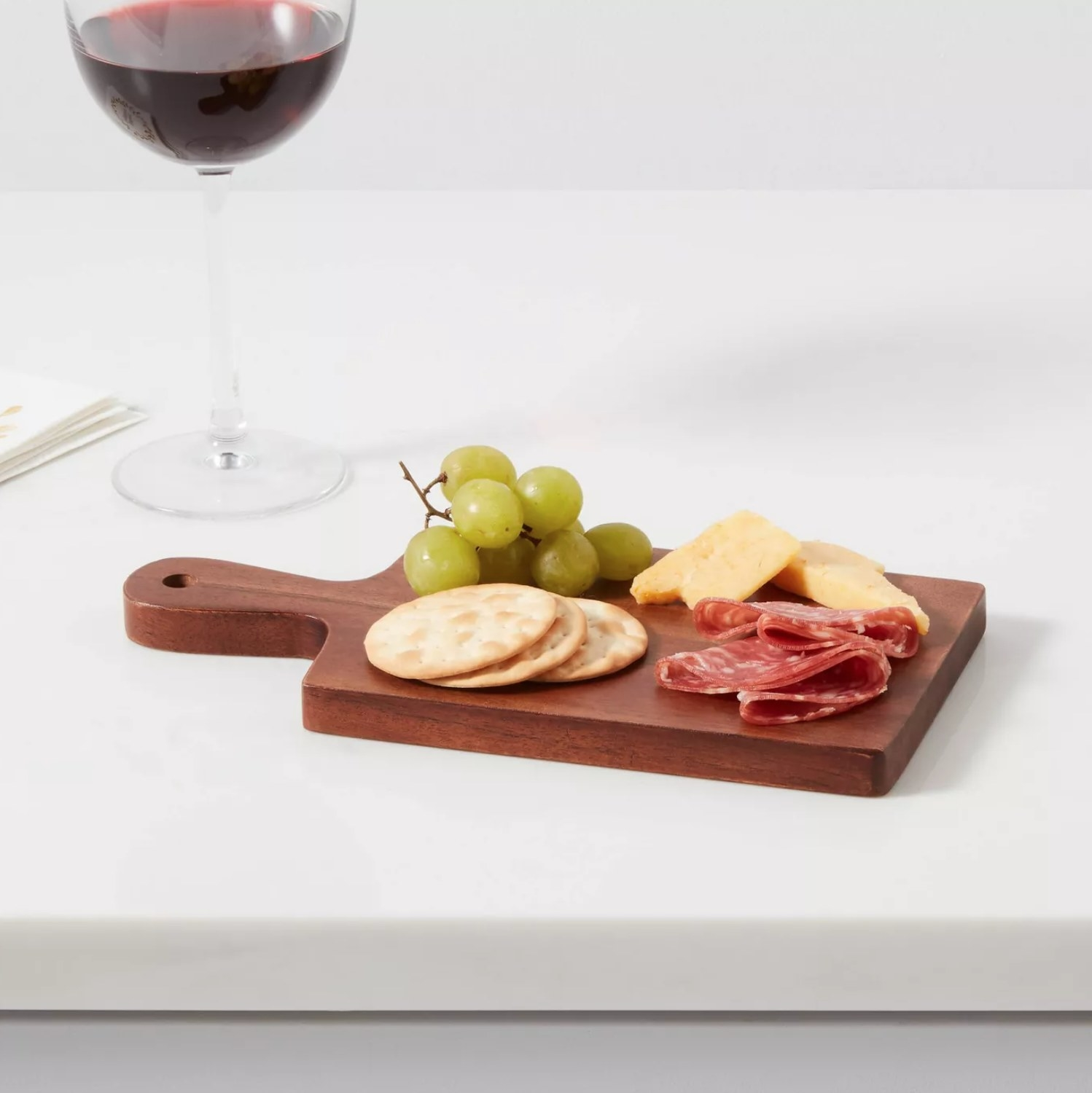 the brown tray with salami, cheese, crackers, and grapes on it next to a glass of red wine