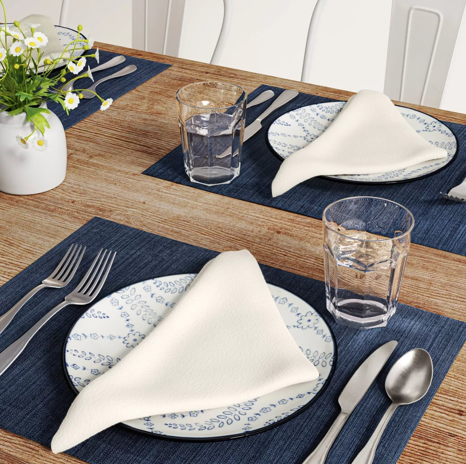 the white cloth napkins on blue and white plates on top of blue placemats with silverware and water glasses on a wooden table