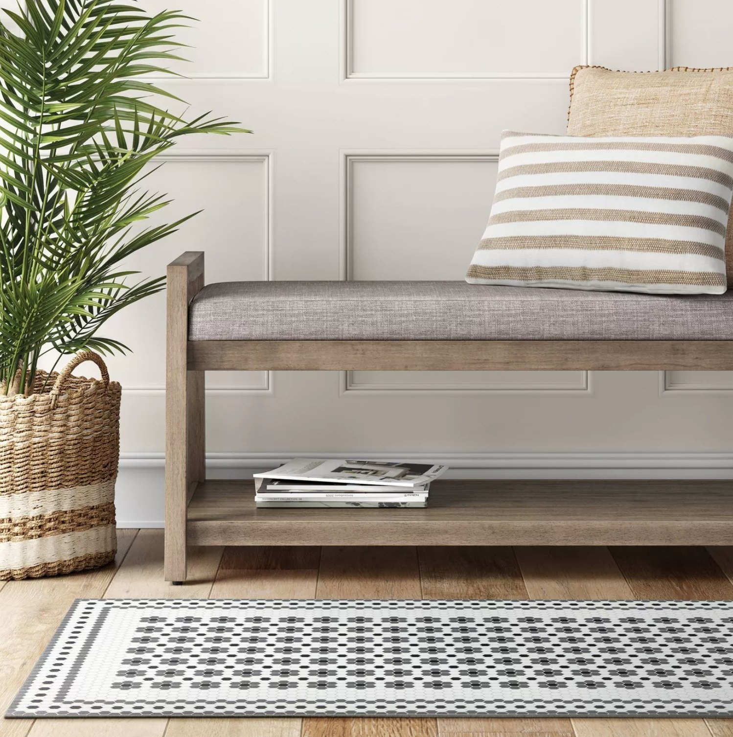 the gray and white tile mat on a wooden floor with a bench next to it with magazines on the bottom shelf and throw pillow on the bench top
