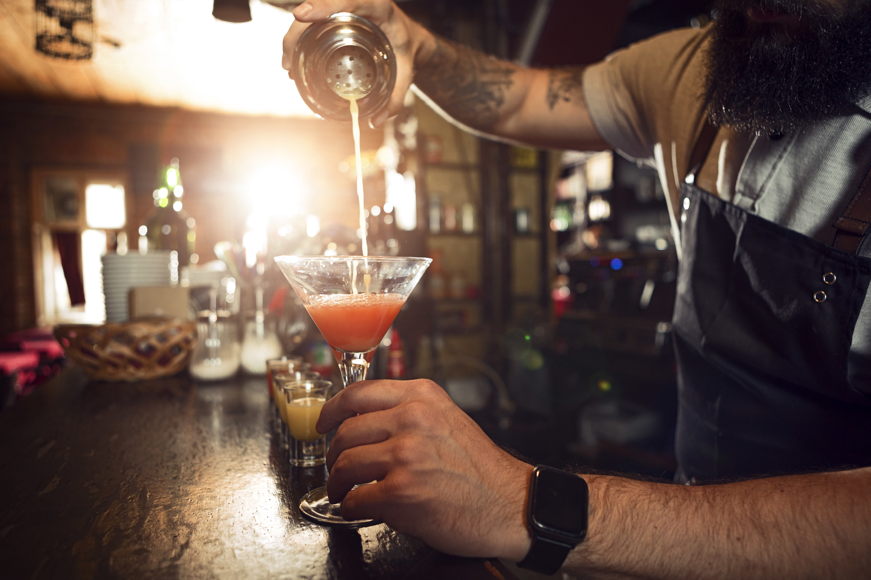 Bartender pouring a frothy drink into a martini glass.