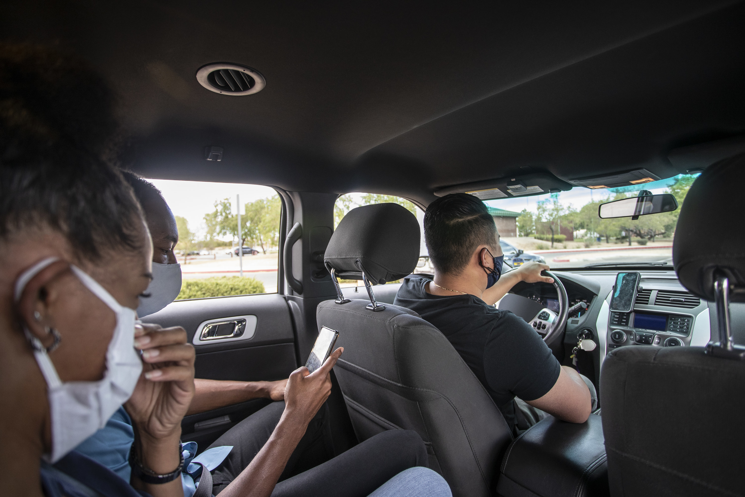 Uber driver driving with two passengers in the back seat.