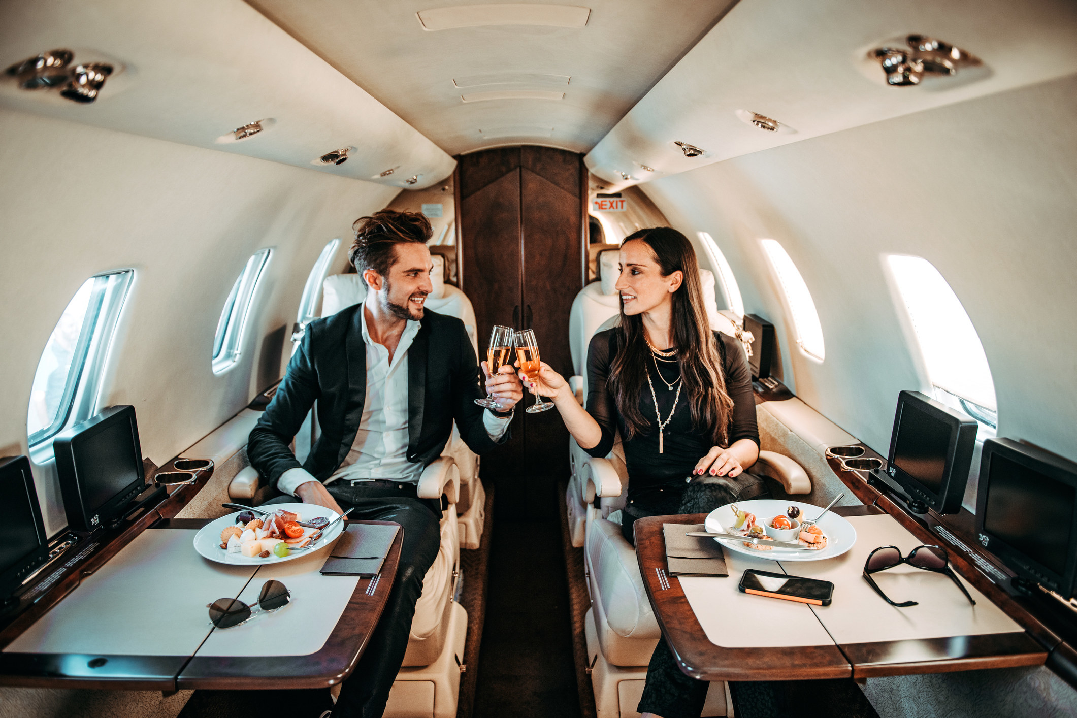 Rich couple making a toast with champagne glasses while eating canapés aboard a private jet