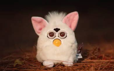 a white furby on some grass staring into the abyss