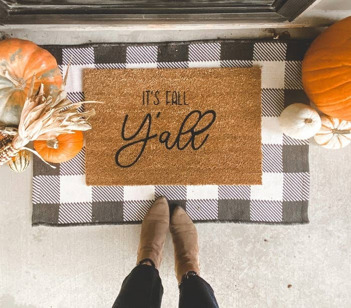 """A coir doormat with the words """"It's Fall Y'all"""" on it in black, surrounded by pumpkins on either side and a black-and-white checkered mat underneath. A person's legs are visible in front of the mat."""