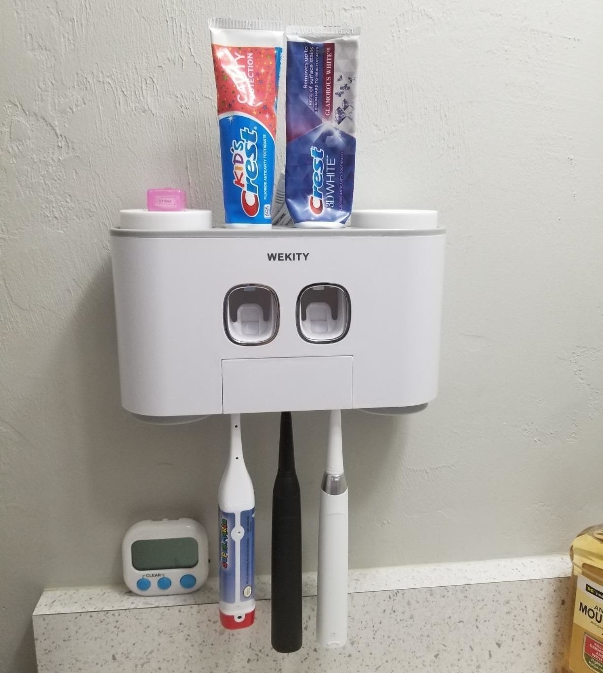 a reviewer photo of the wall-mounted station with three toothbrushes hanging from the bottom and two tubes of toothpaste inserted on the top