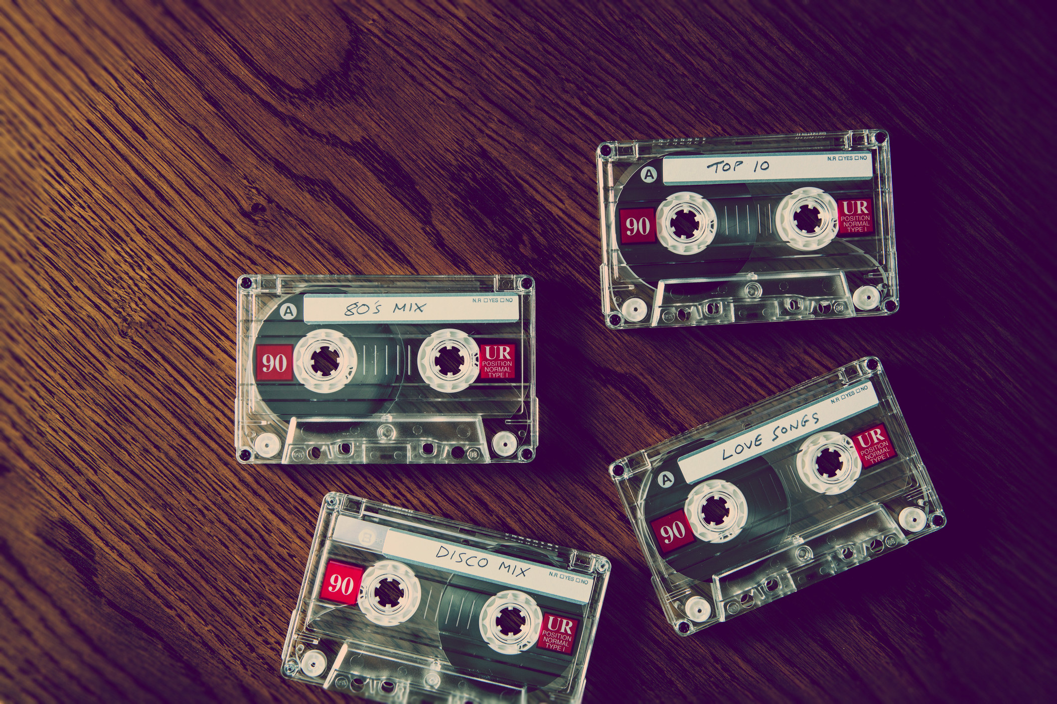 four casette tapes on a wooden able