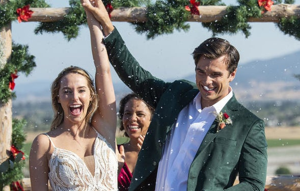 Two people holding their arms up in celebration after just getting married