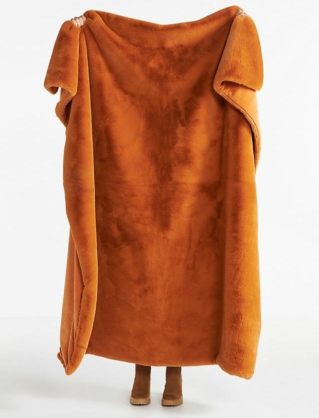 An orange blanket being held up in front of someone, covering their entire body
