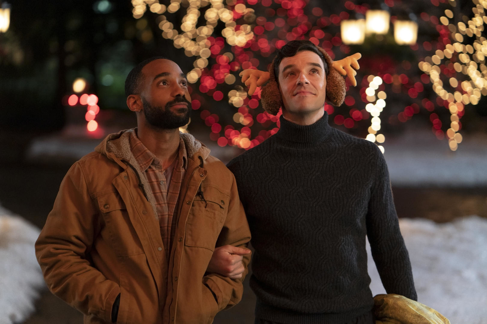 Peter, who's wearing reindeer earmuffs, stands arm-in-arm with James outside