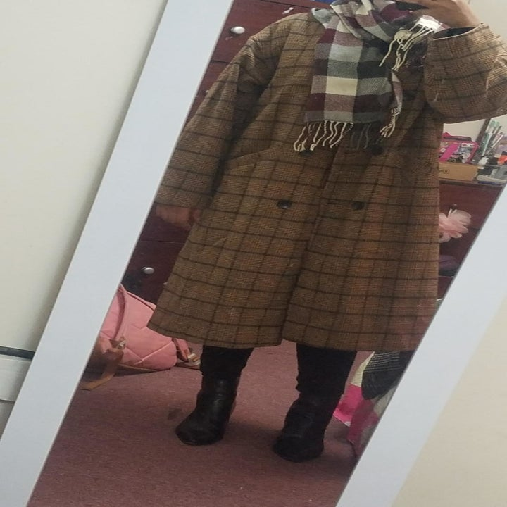 reviewer wearing the coat with a scarf