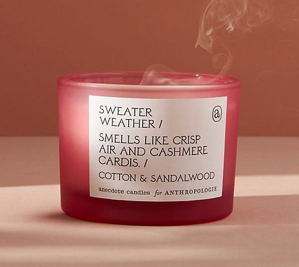 """A red candle with a white label that says """"Sweater Weather / Smells like crisp air and cashmere cardis / Cotton & sandalwood"""""""