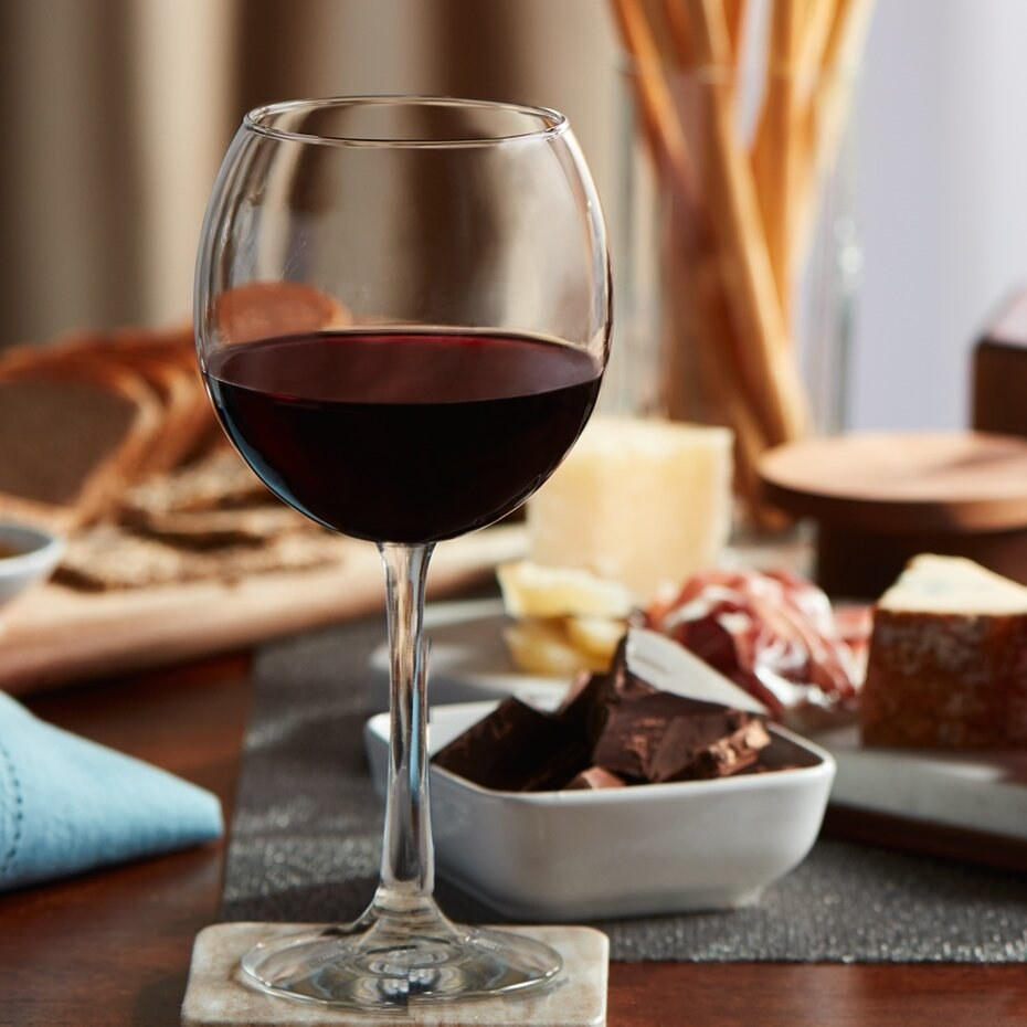 Photo of wine glass filled with red wine, with charcuterie in the background