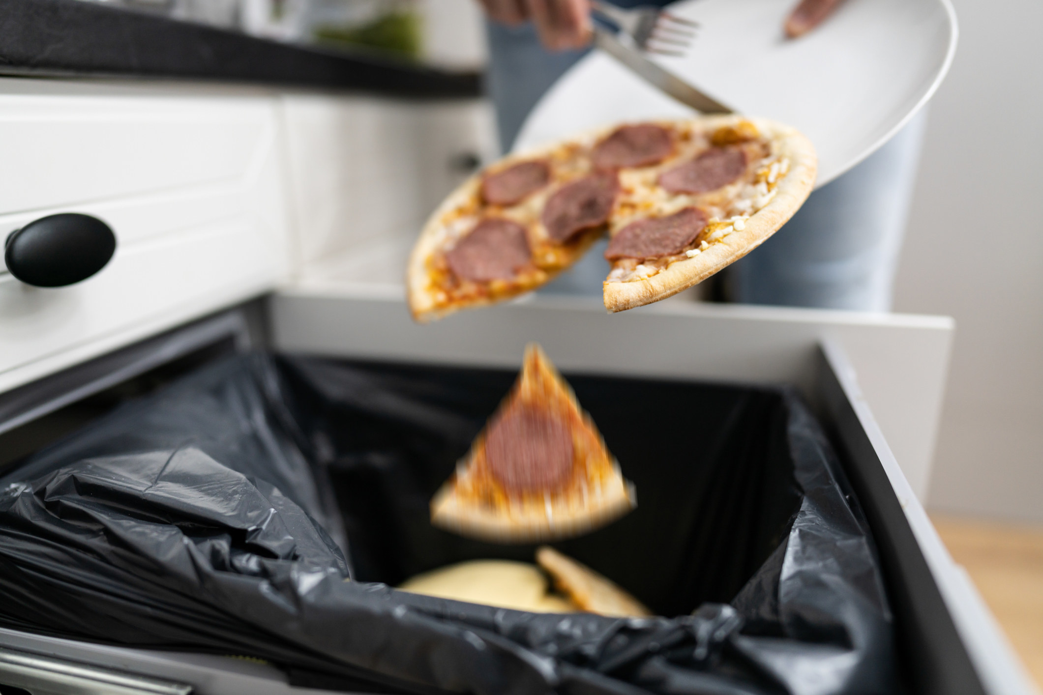 Pizza being thrown out in the trash