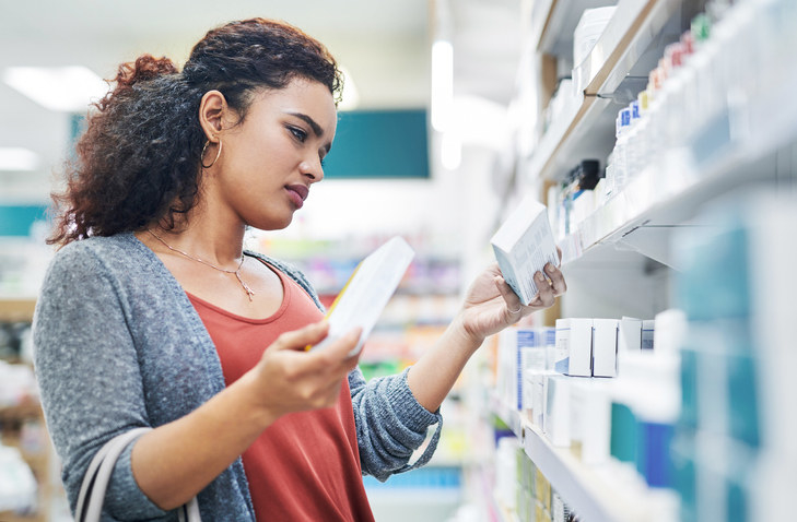 A woman standing in a pharmacy aisle comparing two boxes