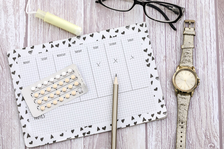 A calendar surrounded by EC pills, a watch, a pair of eyeglasses, and a tampon
