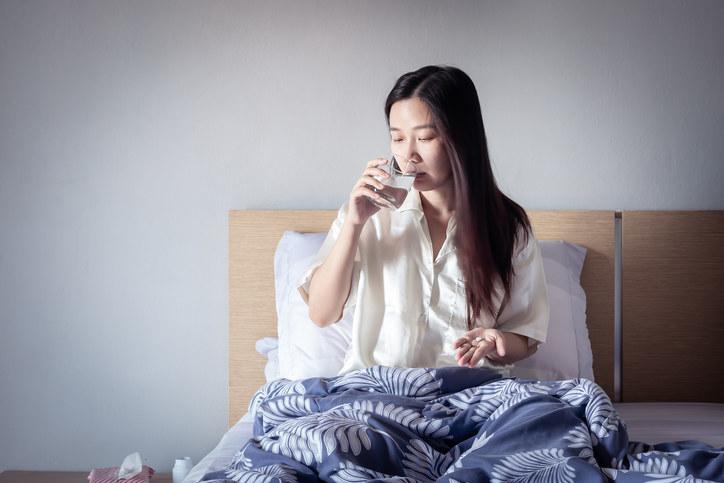 A person sitting in bed and taking a sip of water to go with their pills