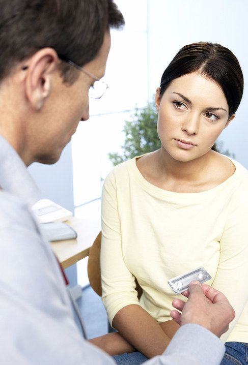 A woman being handed two pills