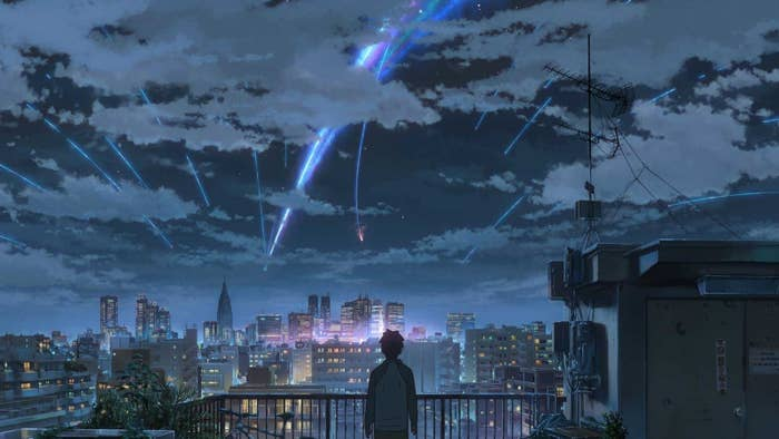 An anime clip of someone overlooking a city while flashing lights shoot from above