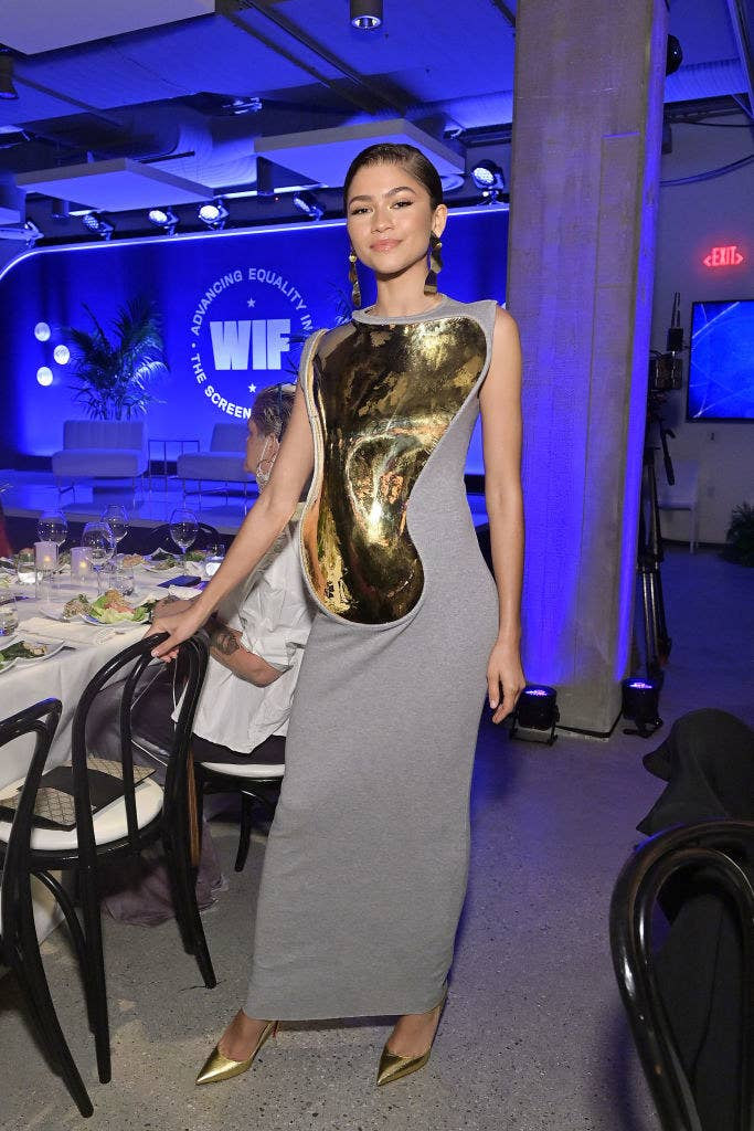 Zendaya posing by a table inside the event