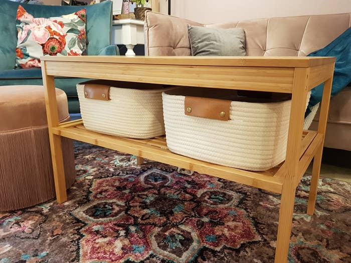 reviewer image of two of the white woven baskets with brown handles on a shelf of a coffee table