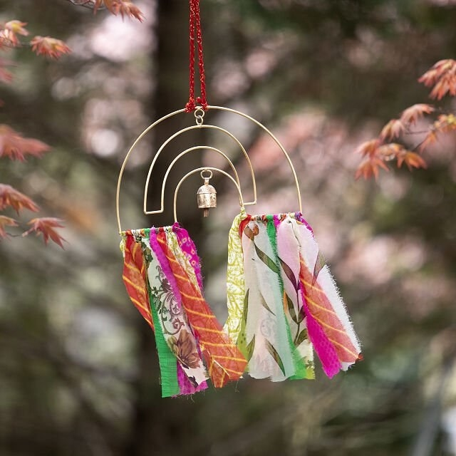 gold metal rainbow with a bell and fabric in several colors hanging from the bottom