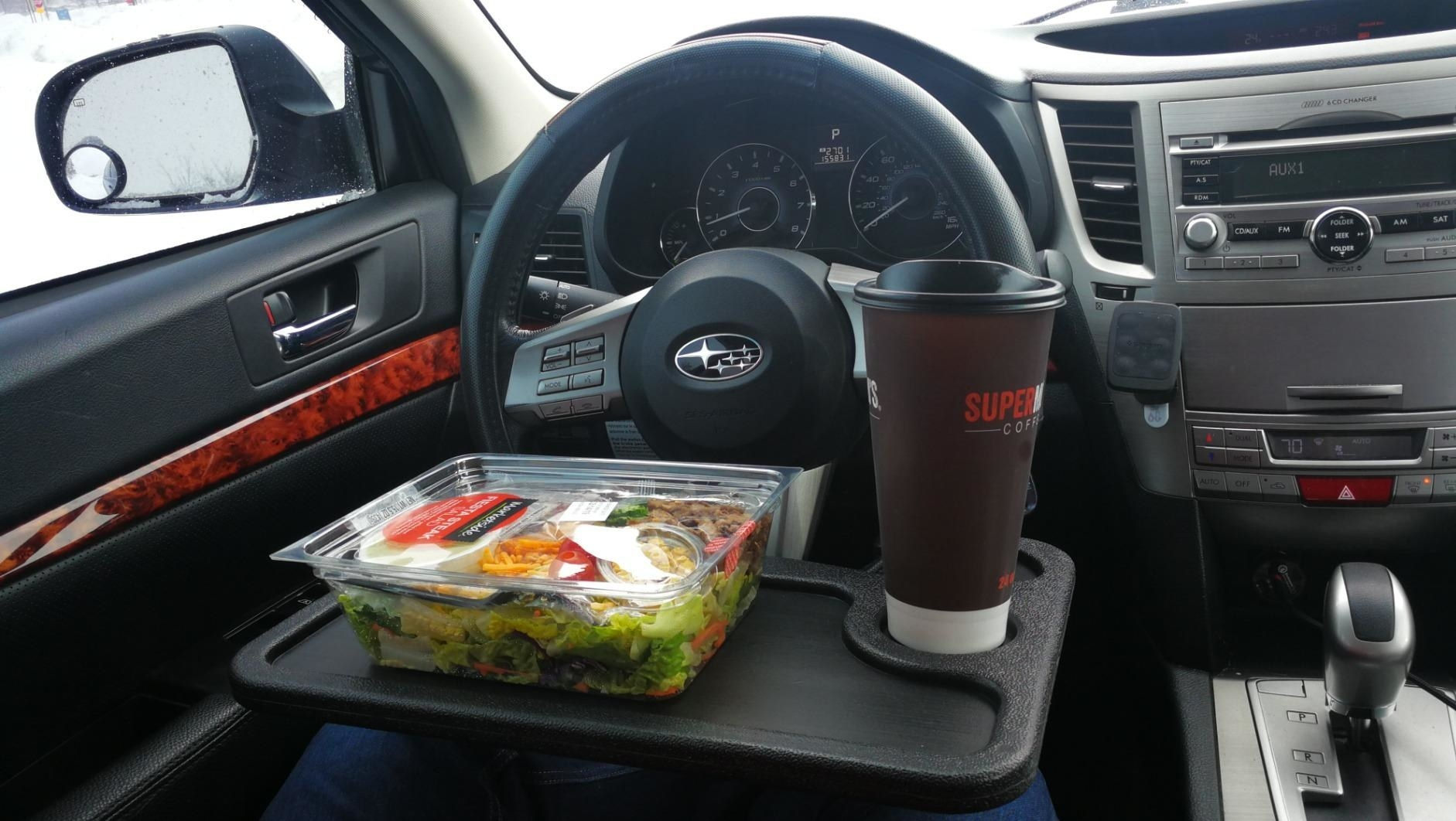 reviewer image of the black tray attached to the steering wheel with a salad and coffee cup on the tray