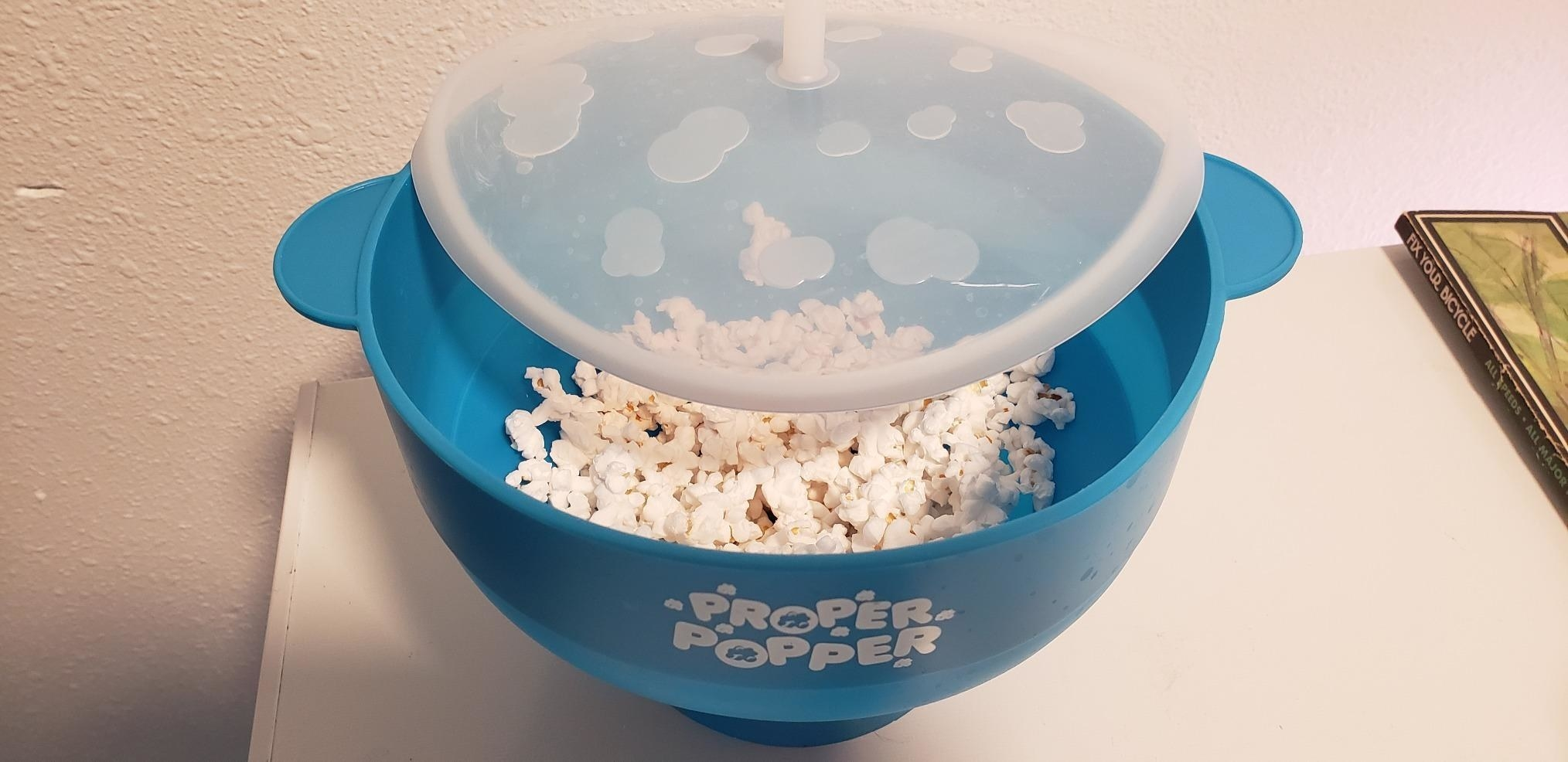 image of the popcorn maker in blue with popped popcorn inside and the silicone lid partly off the top