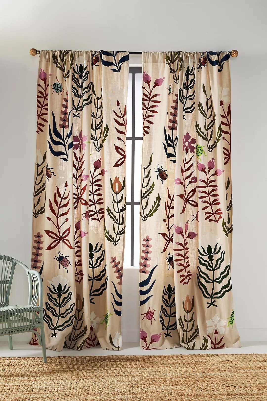 tan curtains with colorful flowers and bugs embroidered on top