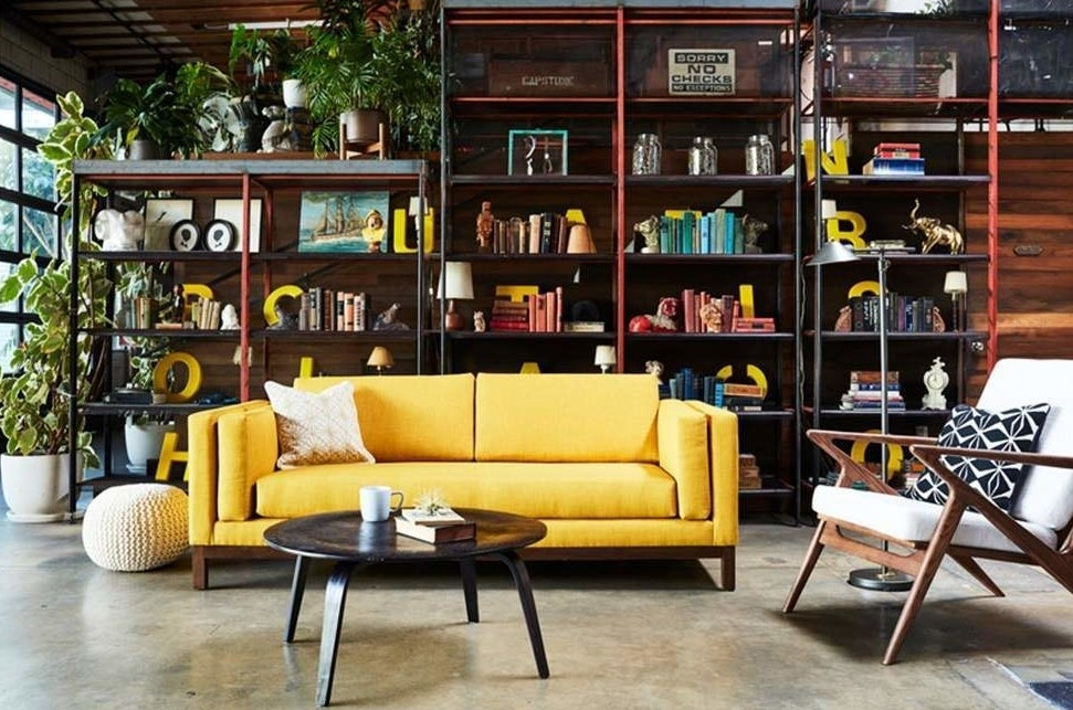bright yellow sofa with cushioned armrests between the padded frame and seat cushion