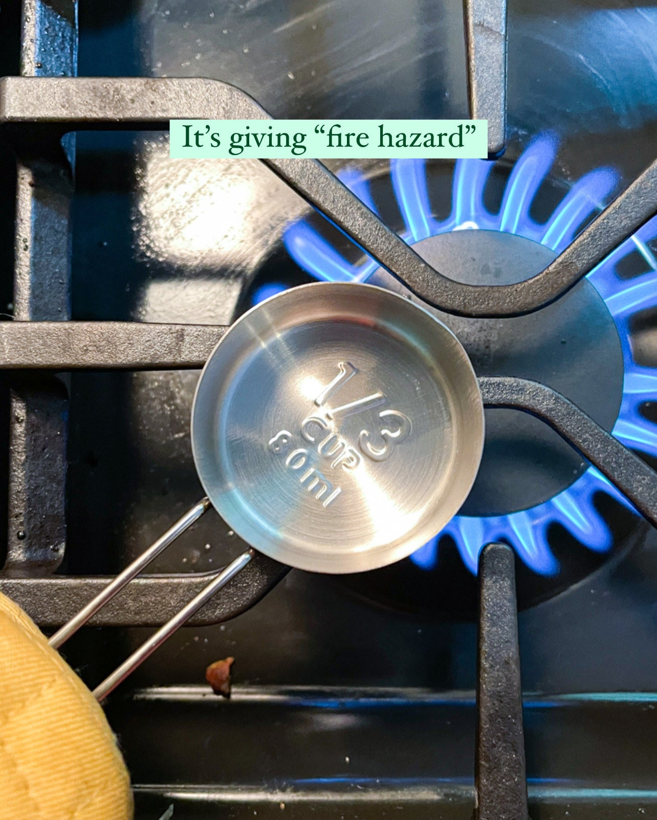 stainless steel measuring cup placed over the flame on a stove