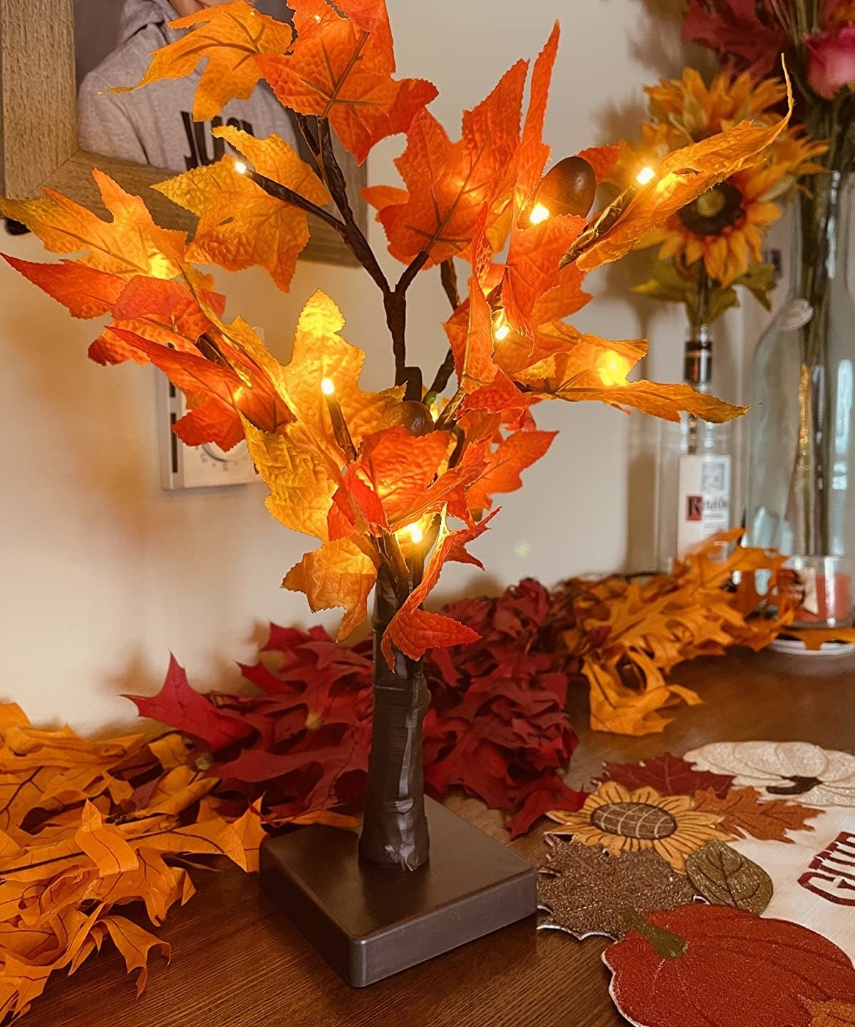 A fake light-up tree with orange and red flowers on a brown tabletop next to more fake leaves
