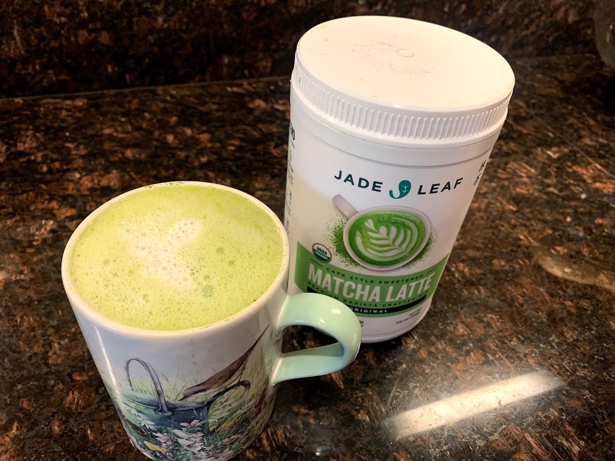 the jug of matcha powder on a counter with a matcha drink in a mug in front of it