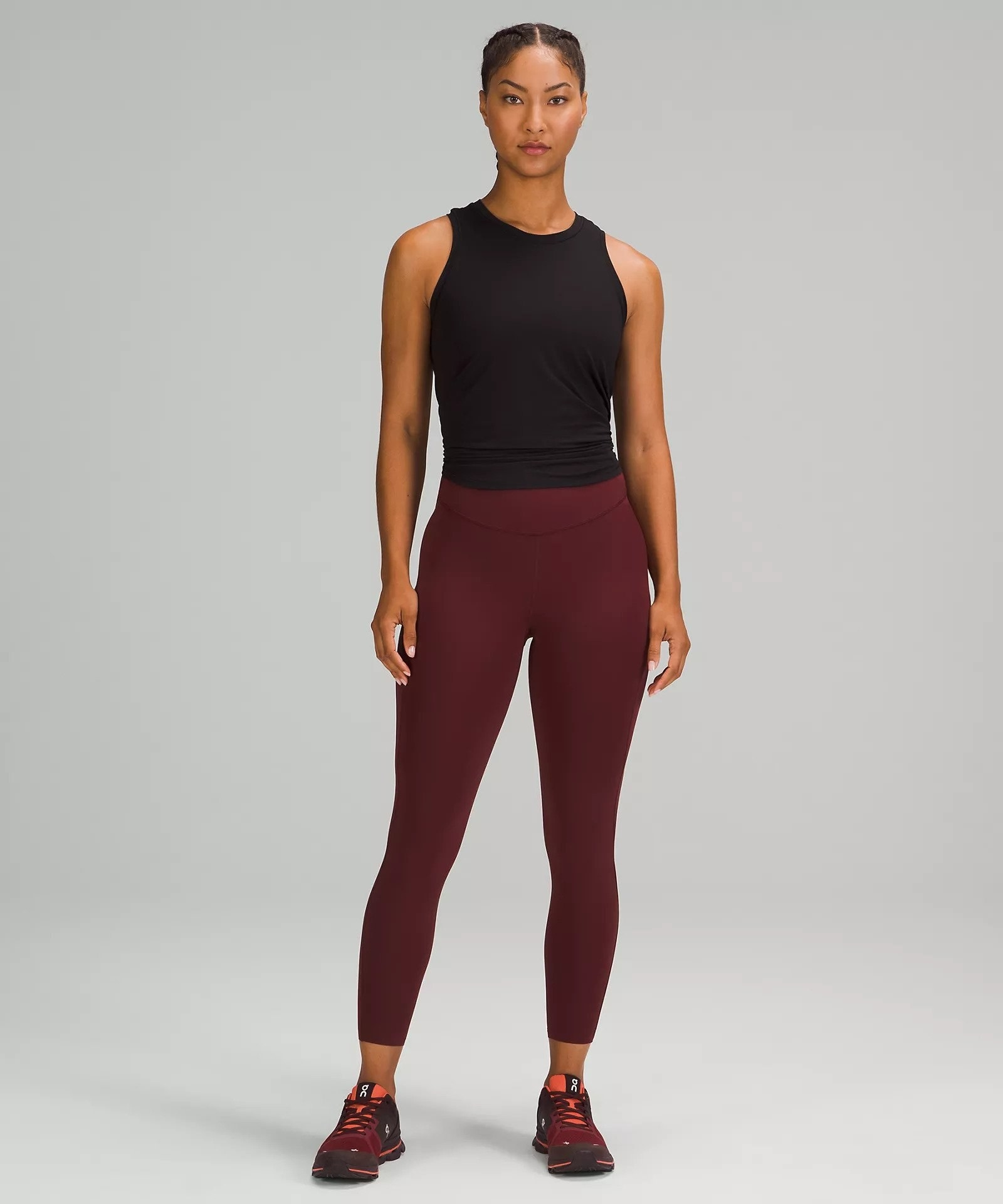 model in dark red cropped high-rise running tights and a black workout tank top