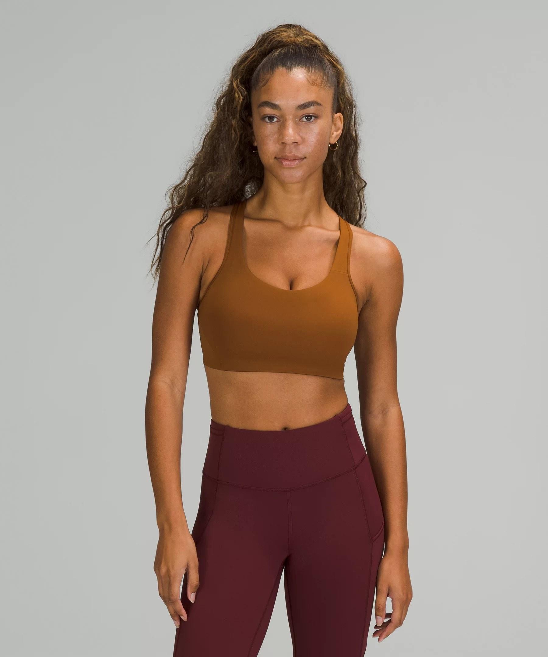 model in copper brown sports bra and berry leggings