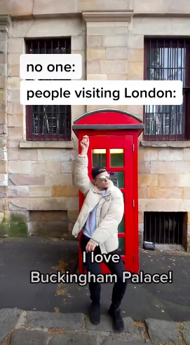 """Pavel standing in front of an old school telephone booth with the caption """"I love Buckingham Palace!"""""""