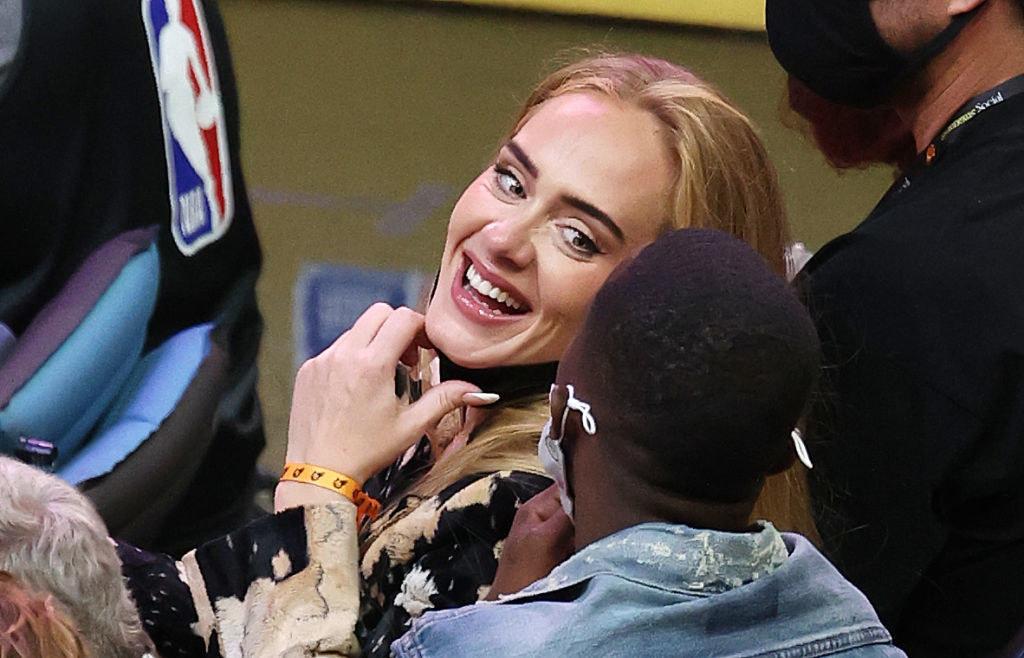 Adele smiling at someone sitting behind her at an NBA basketball game