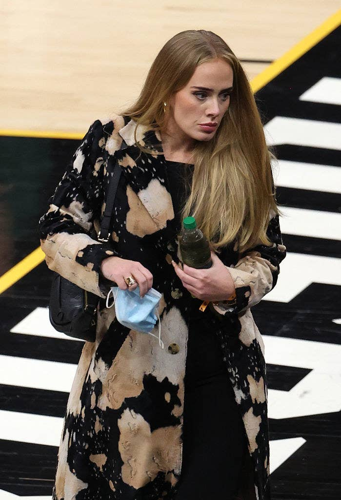 Adele walking at an NBA basketball game and holding a water bottle and a face mask