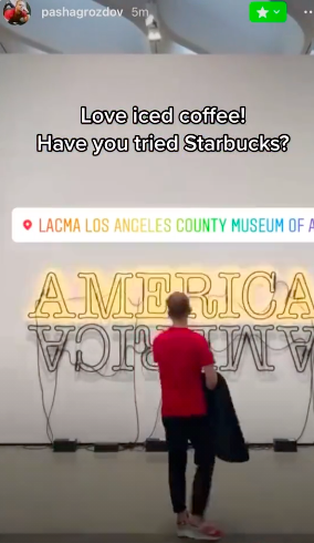 """Pavel looking at a neon sign that says America at a museum with the caption """"Love iced coffee! Have you tried Starbucks?"""""""