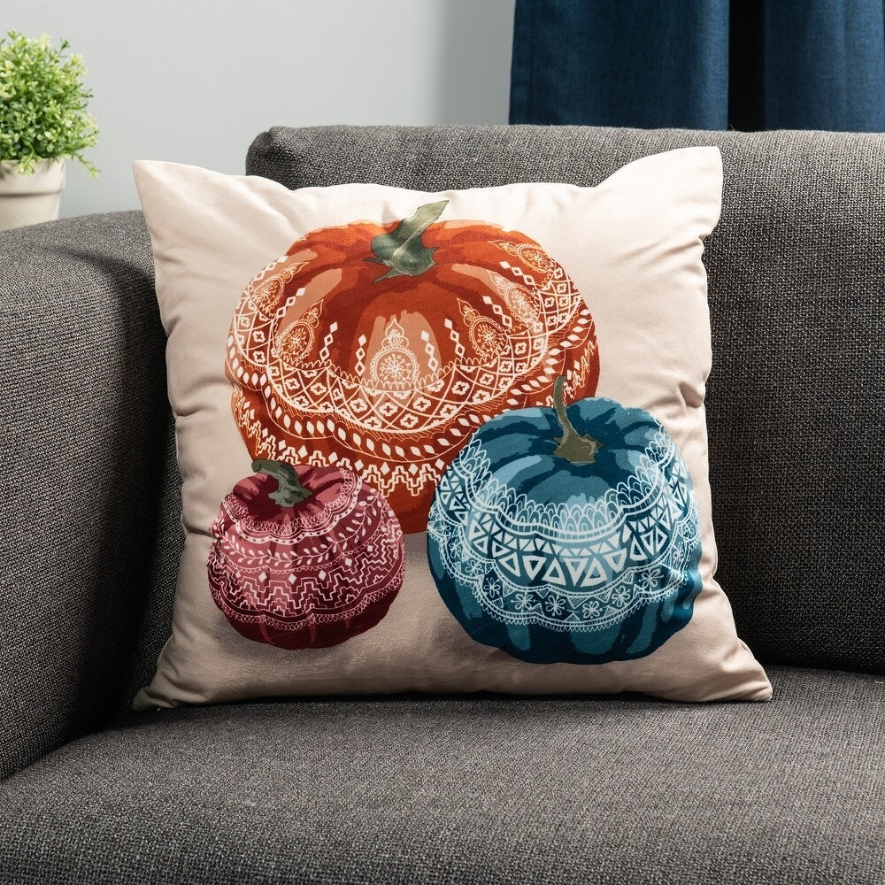 A white velvet pillow with pumpkins on it in three different colors (orange, blue, and garnet)