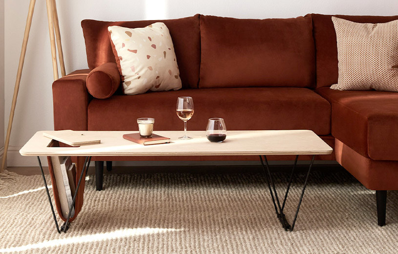 the wood-top coffee table with metal v-shaped legs and a storage area on the left side