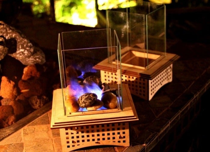 A mini tabletop glass fireplace burning