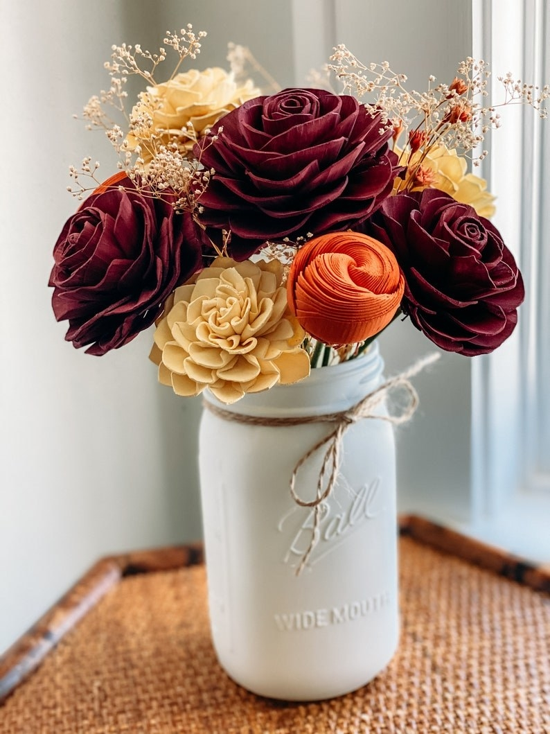 A fall bouquet of dark red, orange, and beige wooden flowers in a white Mason jar