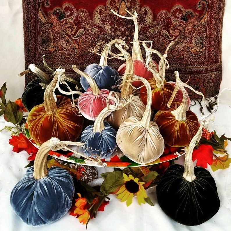 A pile of different-colored velvet pumpkins with golden stems