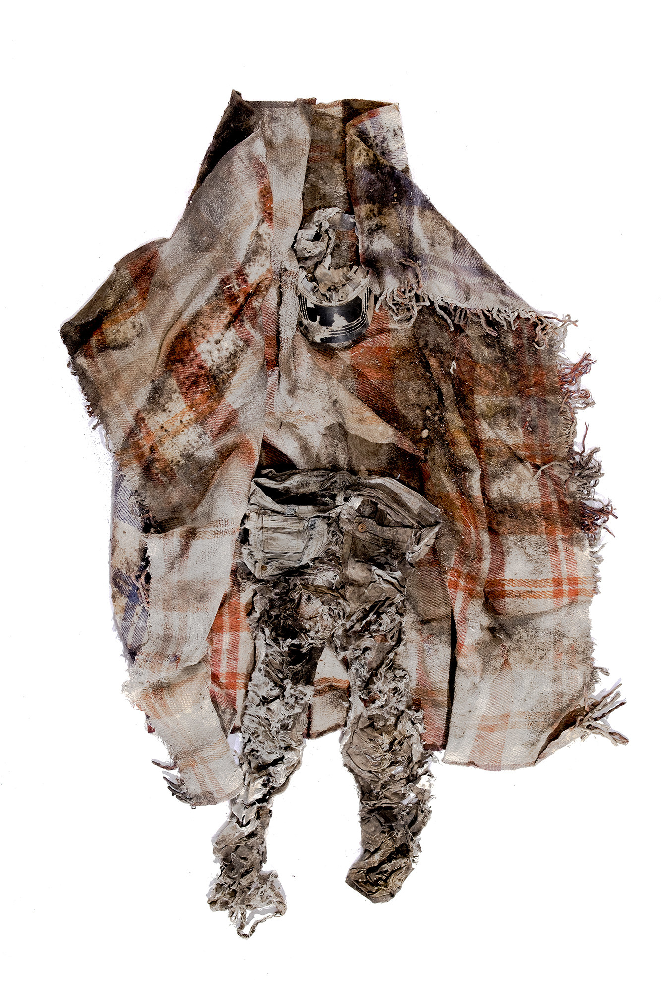 A torn, stained, blanket and pieces of clothing