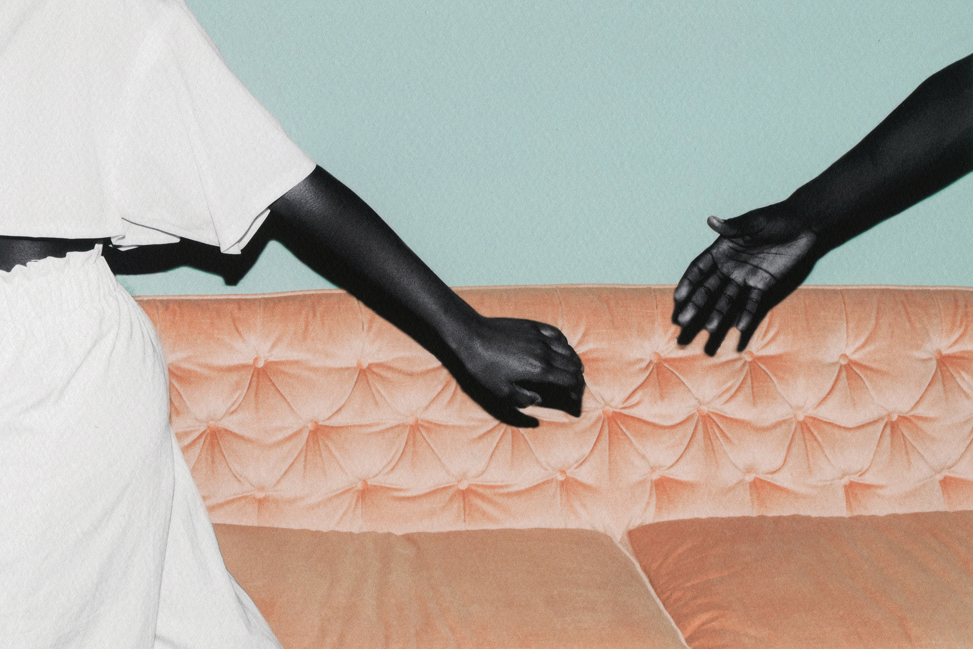 Man is reaching for a woman's hand as she is letting him go, their arms shown against a sofa background